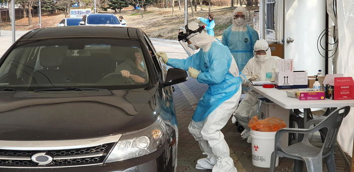A medical worker collects a sample from a citizen in an automobile at a drive-thru clinic in Cheonan, 29 February 2020, to test for the new coronavirus.  ANSA/YONHAP SOUTH KOREA OUT